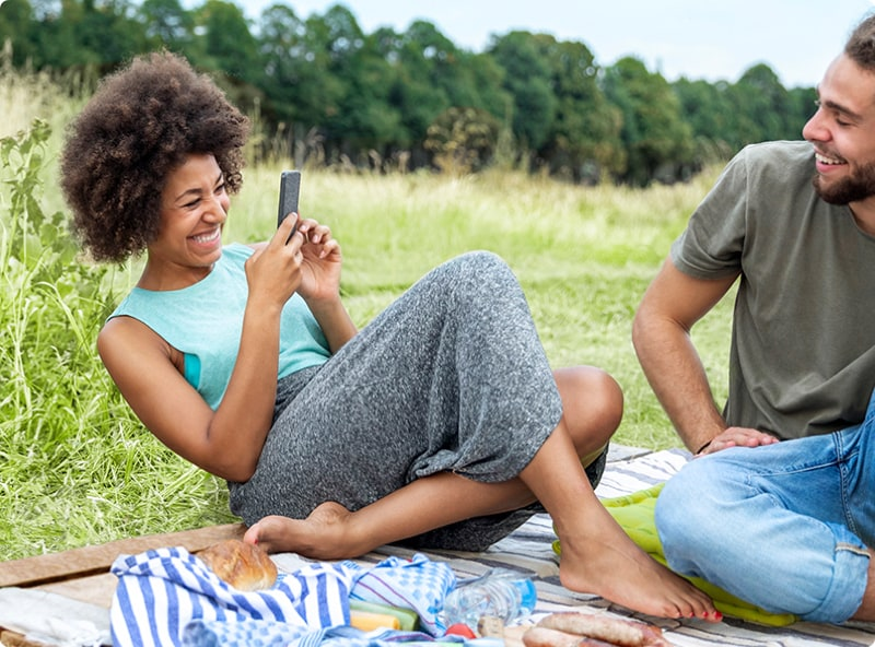 A woman and her partner on a picnic blanket